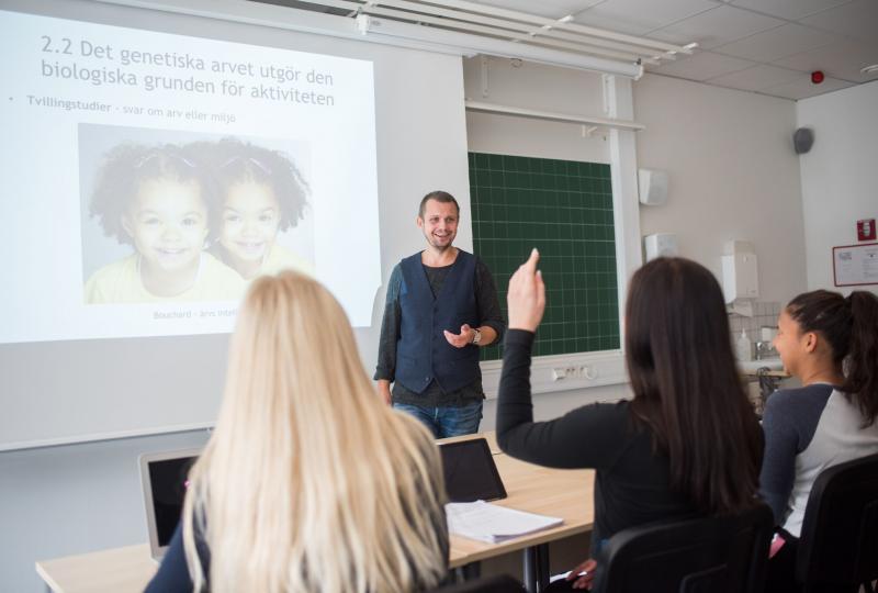 Glada studerande och lärare i klassrum
