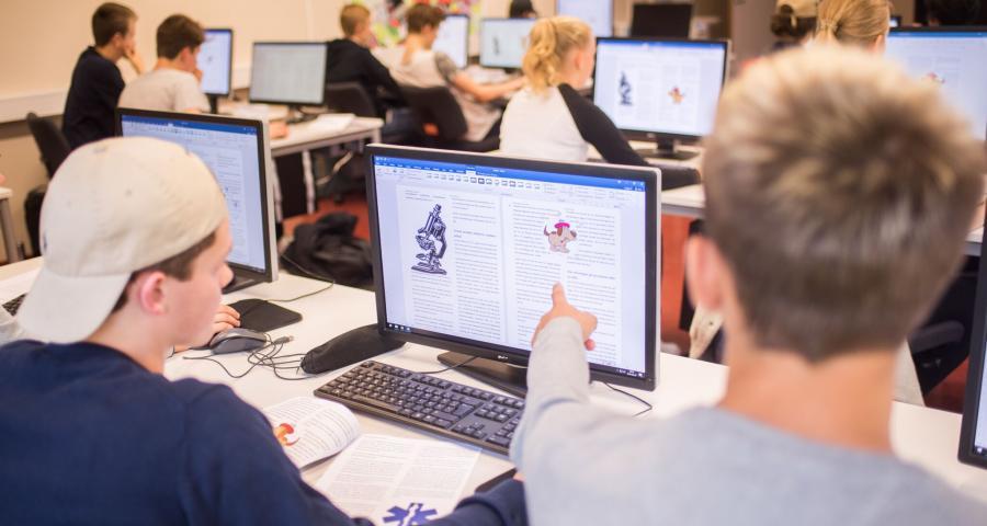 Studerande vid dator i klassrum